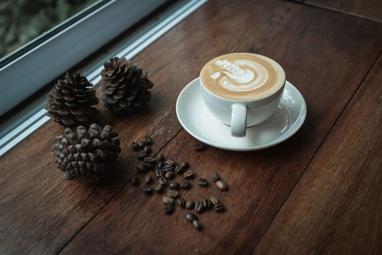 Pine Cones Cappuccino Coffee Coffee - Drink Coffee Cup Crockery Cup Drink Food And Drink Freshness Frothy Drink High Angle View Indoors  Latte No People Non-alcoholic Beverage Refreshment Still Life Table Wood - Material