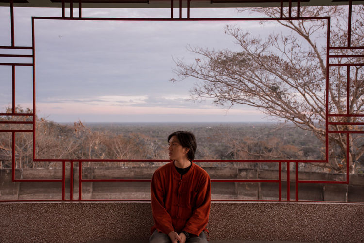 Young Man Sitting On Seat Against Cloudy Sky During Sunset