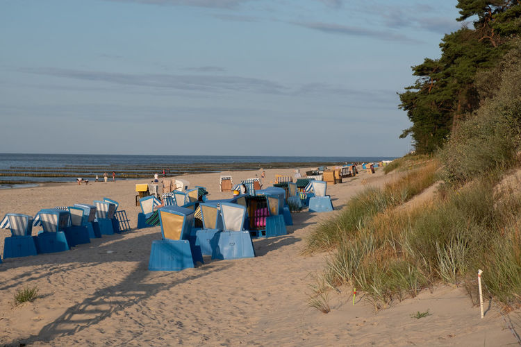 Rear view of hooded beach chairs on shore against sky