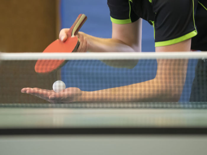 Table Tennis Player serving, focus at the ball behind the net Ball Competition Day Holding Human Body Part Indoors  Leisure Activity Lifestyles Men One Person Playing Preparation  Racket Real People Selective Focus Sport Sports Equipment Standing Table Tennis