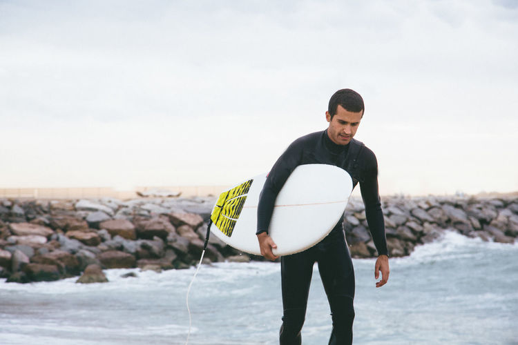 Man carrying surfboard while walking on shore at beach