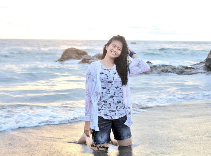 Full length portrait of smiling girl kneeling at beach