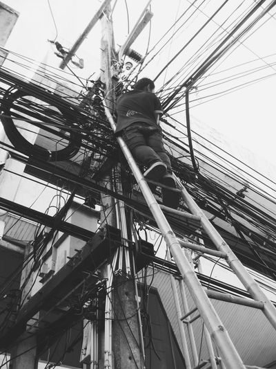 Cable repair asian style Low Angle View Power Line  Power Supply Technology Asian Culture Asian  Lines And Curves Blackandwhite Black And White Black & White Black And White Photography Thailand Travel Thailand Explore Asia Thai Culture Repair Repairing Repairman Only In Thailand Only In Asia Dangerous Lines Cables Power Cable Street Photography