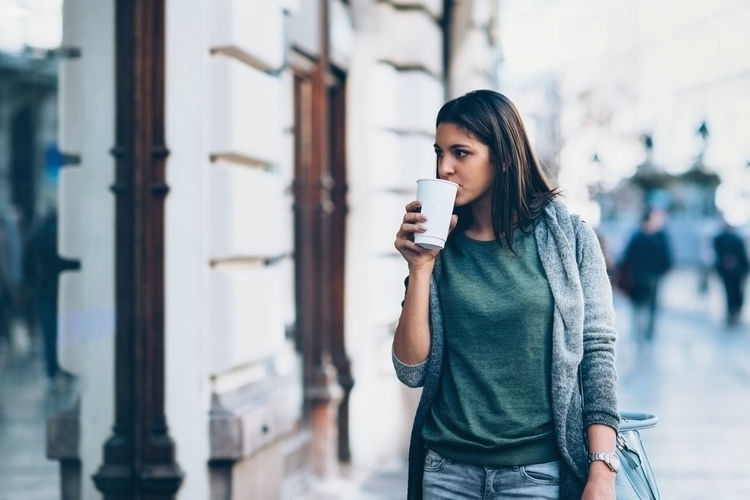 Young Woman Drinking Coffee While Looking Away In City