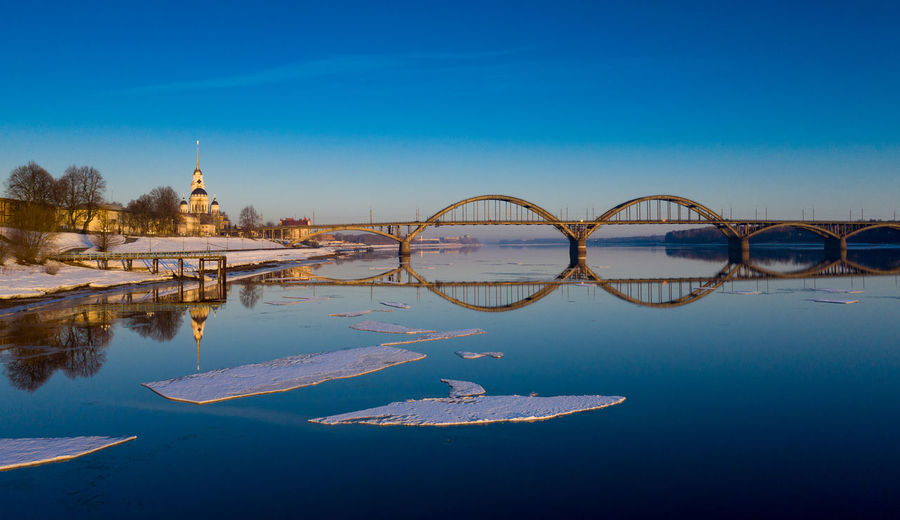 Reflection of bridge in water against clear blue sky