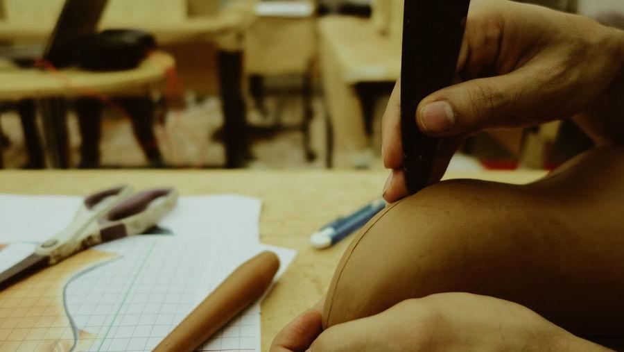 Cropped hands of craftsman carving sculpture in workshop