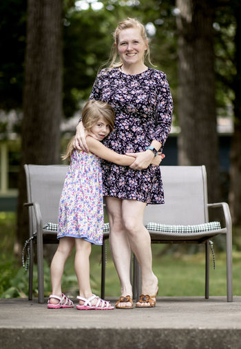 A mother and daughter in dresses pose for a portrait on a summer morning. Love Mother Beautiful Woman Casual Clothing Child Childhood Daughter Day Emotion Family Females Full Length Girls Hairstyle Innocence Looking At Camera Offspring Outdoors Portrait Real People Sister Smiling Togetherness Two People Women
