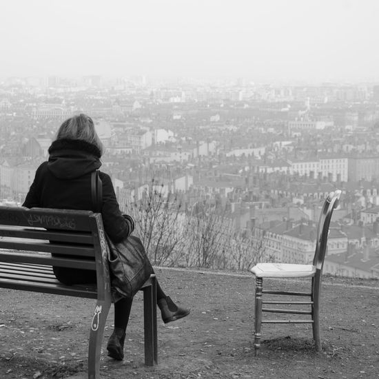 Full length rear view of woman sitting on bench by cityscape during foggy weather