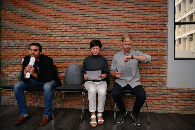 Business people waiting while sitting on chairs against brick wall in office