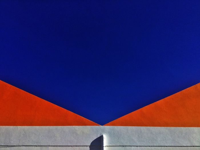 Low angle view of multi colored wall against clear blue sky