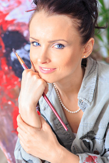 portrait of a female painter at work Adult Adult, Art, Artist, Artistic, Artwork, Beautiful, Brush, Canvas, Creative, Creativity, Drawing, Female, Girl, Hobby, Home, Interior, Lifestyle, Paint, Paintbrush, Painter, Painting, Palette, Person, Portrait, Professional, Studio, Woman, Work, Young Bad Habit Beautiful Woman Beauty Casual Clothing Cigarette  Hairstyle Headshot Holding Leisure Activity Lifestyles Looking At Camera One Person Portrait Smoking - Activity Smoking Issues Social Issues Women Young Adult Young Women
