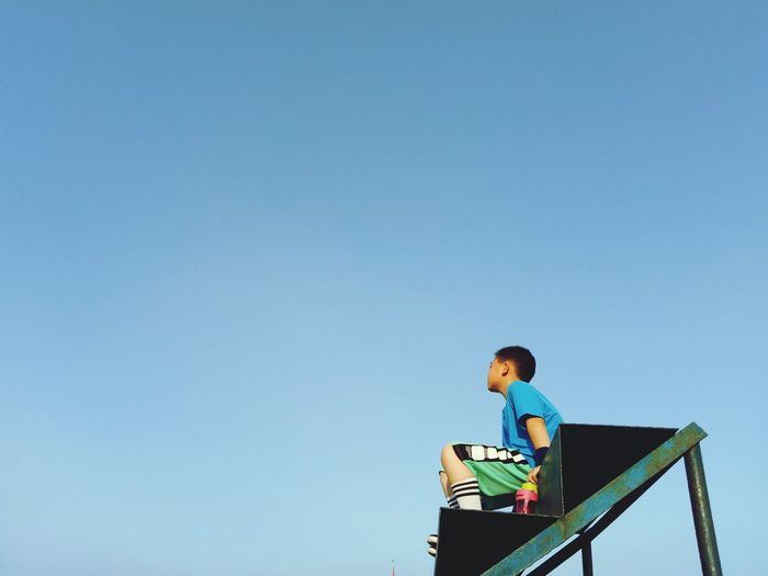 Low Angle View Of Boy Sitting On Steps Against Blue Sky