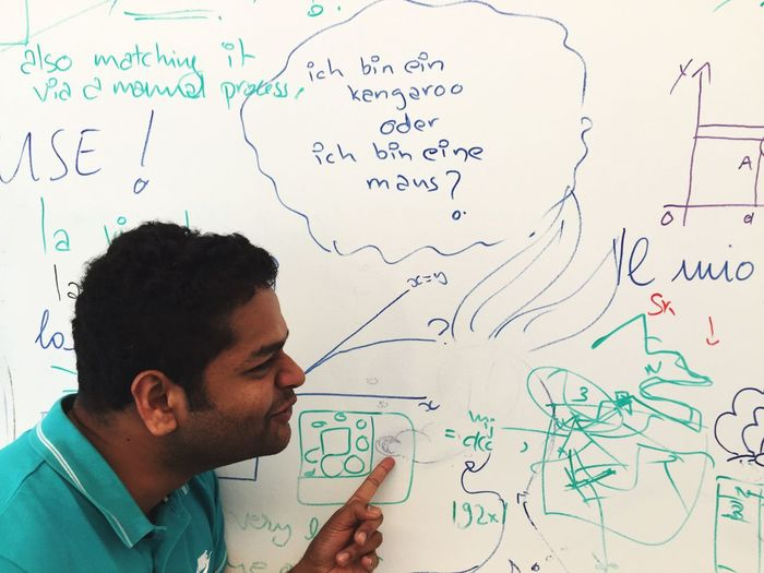 Close-Up Of Confused Man Pointing At Whiteboard