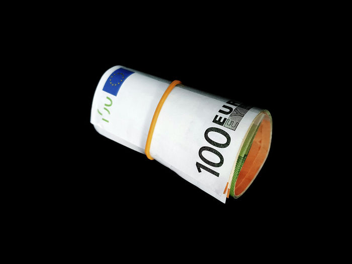 Euro banknotes rolled up on a neutral background Euro Bank Notes Isolated Black Background Bundle Business Close-up Copy Space Curency Currency Cut Out Economy Finance Indoors  No People Number Paper Currency Still Life Studio Shot Text Wealth Western Script