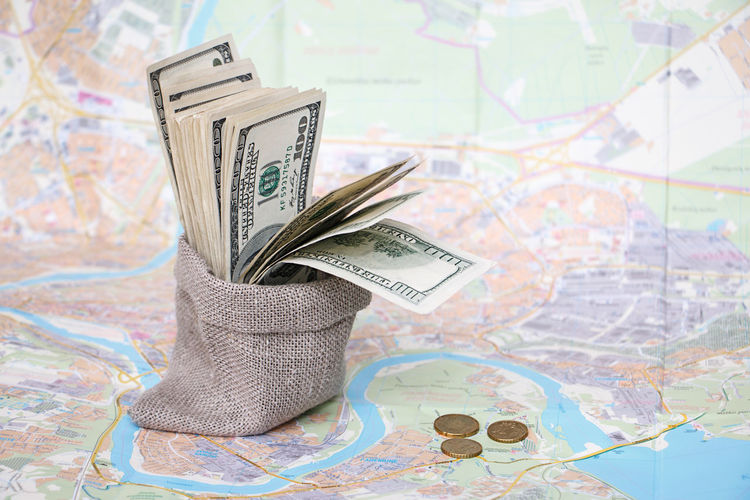 Close-Up Of Paper Currency In Sack On Map