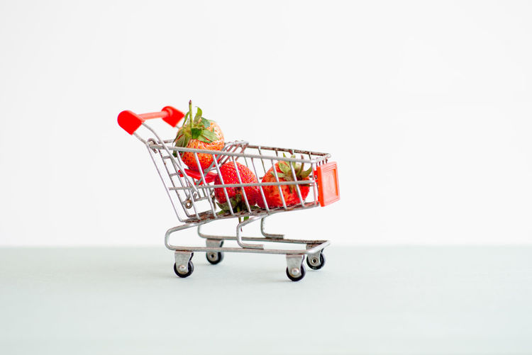 Closeup strawberries in the shopping trolley. Cart carrying the strawberry with the isolated background White Background Shopping Cart Studio Shot Freshness Supermarket Red Shopping Toy