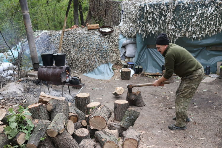 Man cutting logs at forest