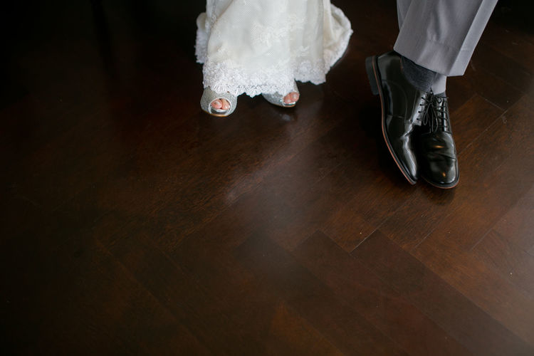 Low section of couple on hardwood floor