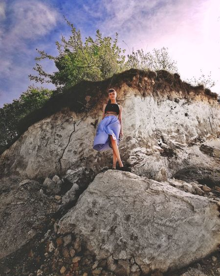 Full length of girl standing on rock against sky