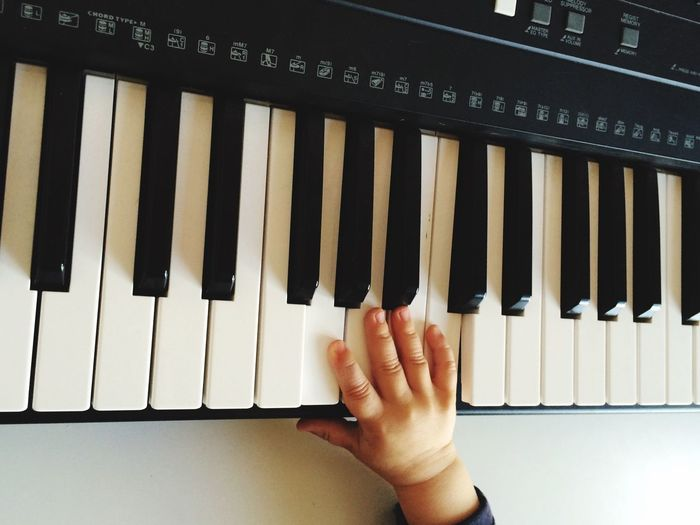 Cropped image of baby boy playing piano