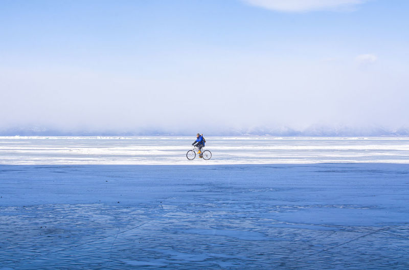 Man riding horse in sea against sky during winter