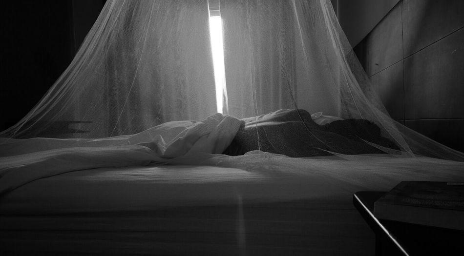 Person sleeping under mosquito net