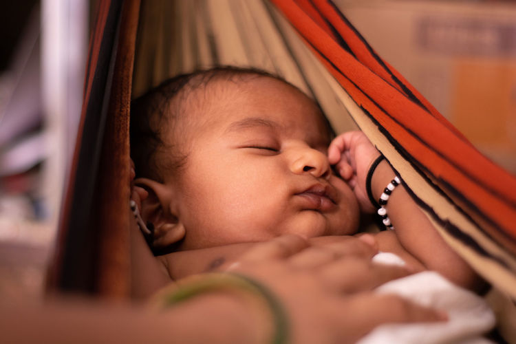 Cropped hands of woman touching cute baby boy sleeping on hammock