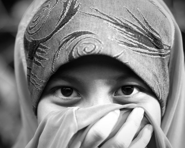 Close-up portrait of girl covering face standing outdoors