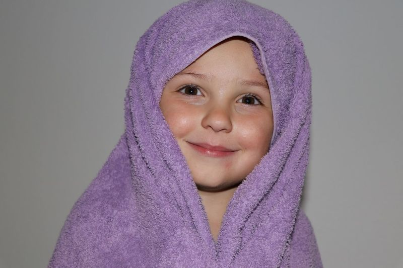 Portrait Of Smiling Girl Wrapped In Towel Against Gray Background