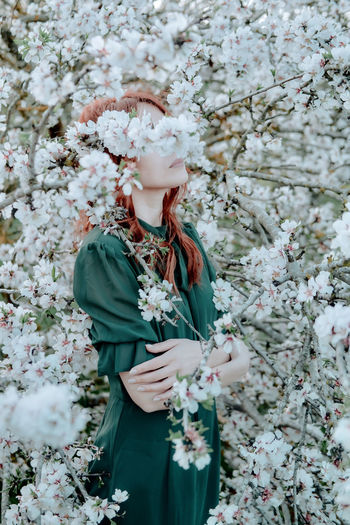 Full length of woman standing by white flowering tree
