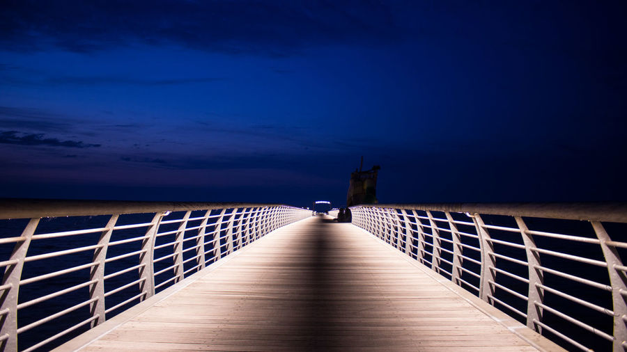 Jetty Leading Towards Sea Against Sky At Night