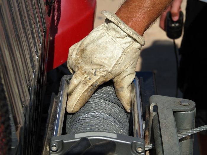 Close-up of manual worker holding steel cable spool on car