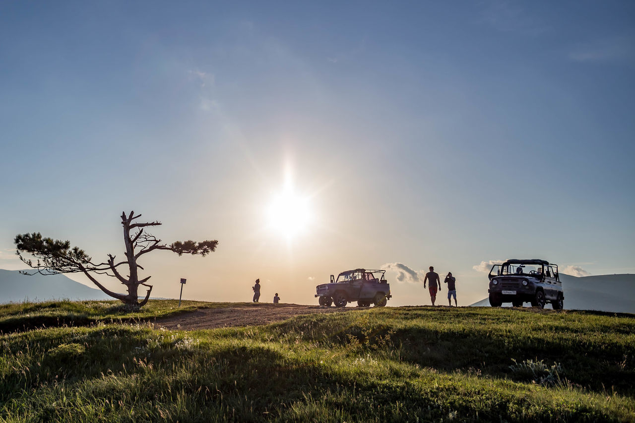 sky, grass, mode of transportation, sunlight, plant, field, land, sun, land vehicle, transportation, nature, landscape, beauty in nature, environment, lens flare, green color, group of people, motor vehicle, car, incidental people, outdoors
