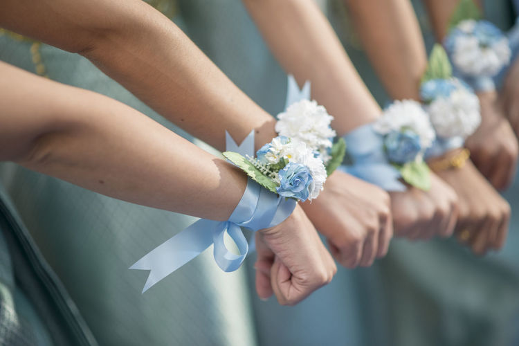Cropped hands of bridegrooms wearing white flowers on hand during wedding