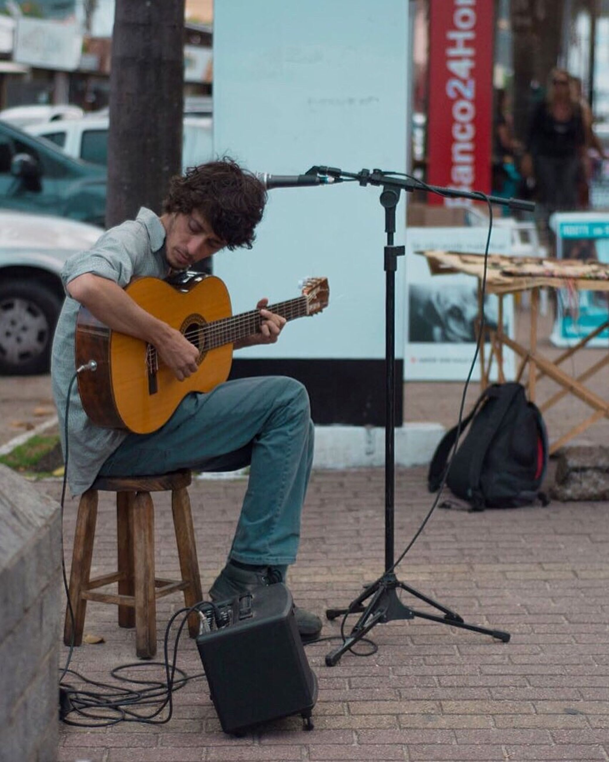 only men, one young man only, music, guitar, plucking an instrument, adults only, one man only, one person, sitting, lifestyles, guitarist, young adult, casual clothing, musical instrument, full length, musician, people, leisure activity, playing, adult, arts culture and entertainment, curly hair, domestic life, men, indoors, performance, day