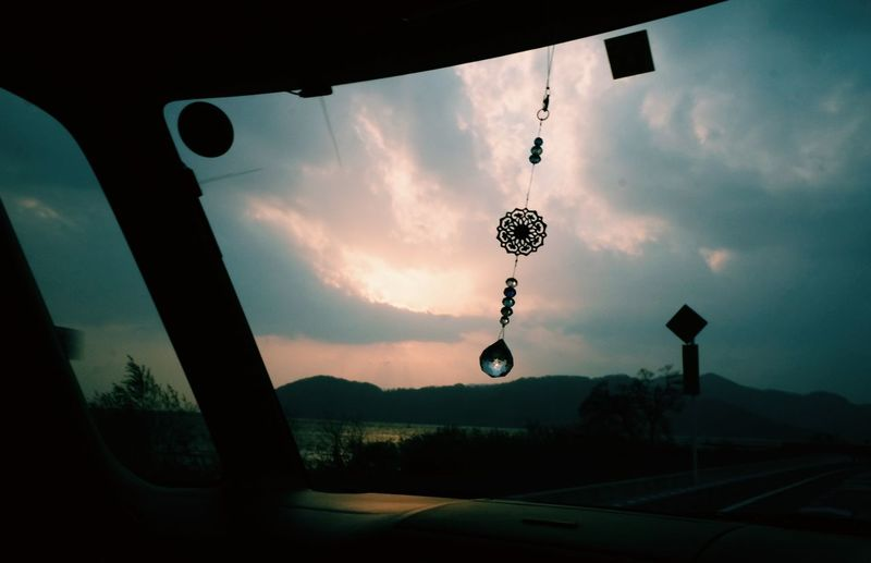 Street light against sky seen through car windshield