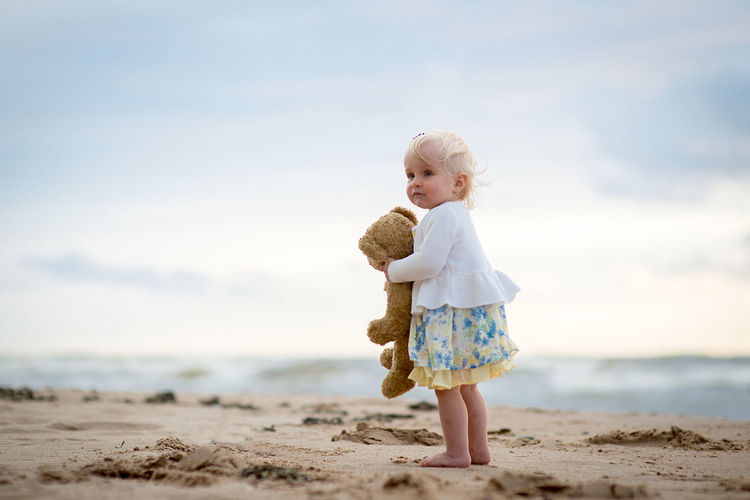 Girl With Stuffed Toy At Beach Against Sky
