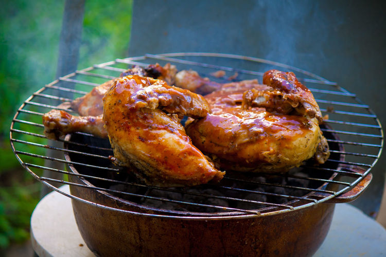 High angle view of chicken meat cooking on metal grate