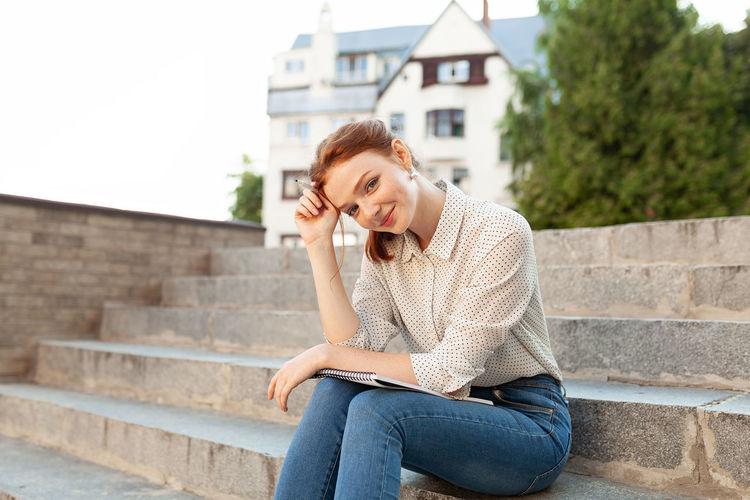 Young beautiful red-haired girl with Jeans Relaxing Student Student Life Students Day Casual Clothing Education Europe Exam Freckles Front View Hairstyle Homework Lifestyles One Person Outdoors Real People Red Hair Sitting Staircase Steps And Staircases Students Life Studying University Young Adult