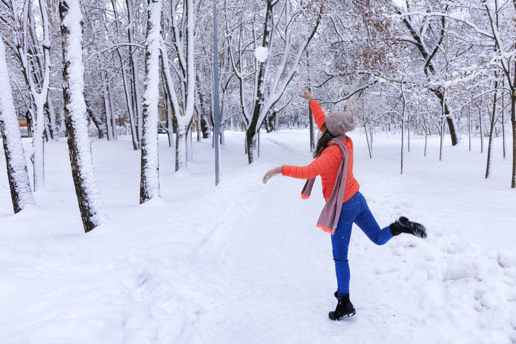 A young beautiful woman in a bright coral jacket and blue jeans in winter walks along the alley of the snow-covered fairy-tale park and throws a large snowball. Winter Snow Cold Temperature Tree One Person Nature Full Length Clothing Land Day Plant Child Warm Clothing Hat White Color Running Childhood Outdoors
