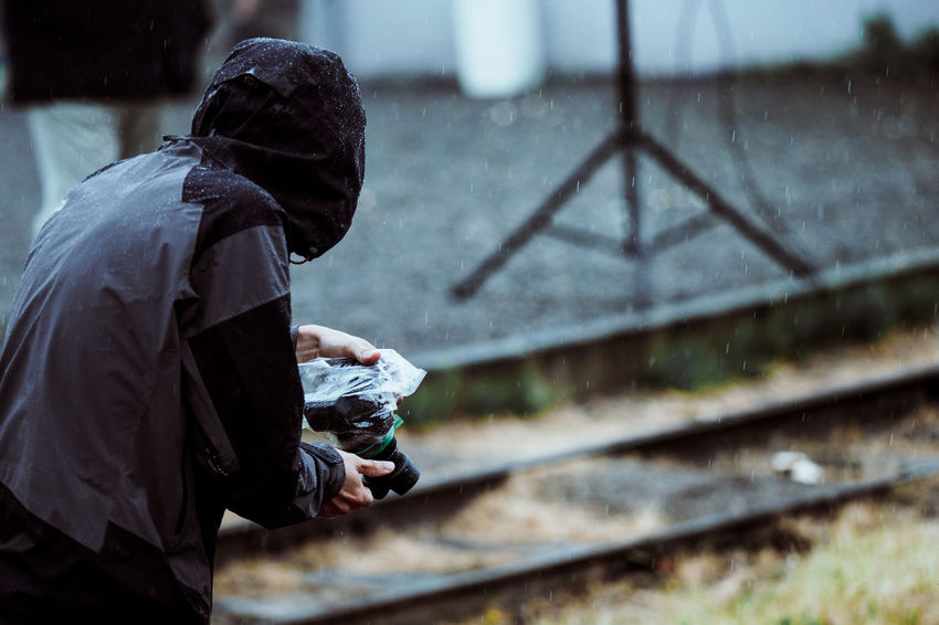 Waterprotected Bad Condition Rain Architecture Clothing Day Focus On Foreground Holding Lifestyles Men Nature One Person Outdoors Photographer Protected Real People Side View Standing Three Quarter Length Track Transportation Unrecognizable Person Waist Up Waterproof Waterproof Camera Wet