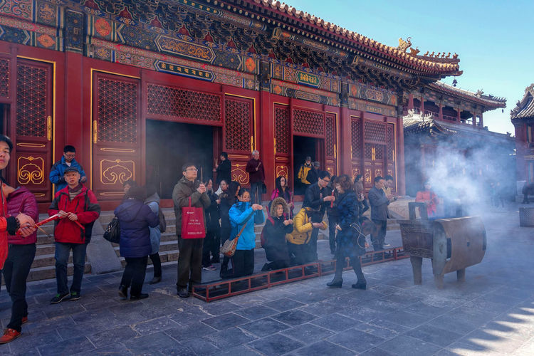 Worshippers hold incense sticks and pray at Yonghegong Lama Temple in Beijing, China. ASIA Beijing Lama Temple Monastery Smoke Worshippers Adult Architecture Budhism Building Building Exterior Built Structure China Crowd Day Entrance Group Of People History Lama Large Group Of People Lifestyles Men Outdoors Place Of Worship Prayer Real People Religion Stick Temple The Past Tourism Travel Travel Destinations Women Yonghe Yonghegong