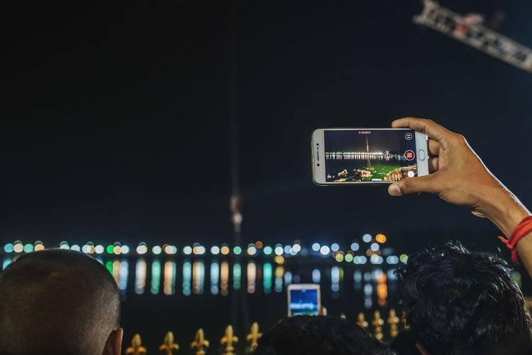 Man Photographing Through Smart Phone At Night