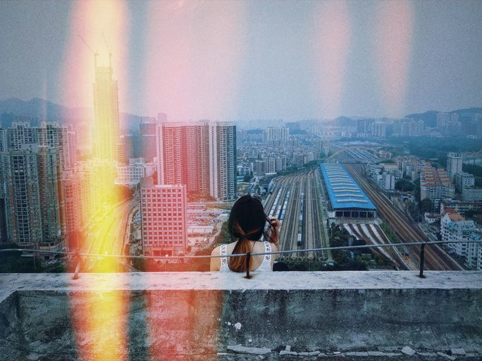 Rear View Of Woman Sitting On Rooftop Against Cityscape