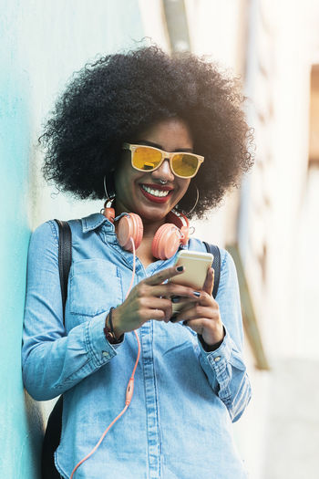 Beautiful afro american woman using mobile in the concept. Adult African Afro American Beautiful City Life Copy Space Hair Headphones Lifestyle Woman Black Casual Clothing Communication Denim Ethnic Hair Mobile Phone Outdoors People Portrait Smart Phone Sunglasses Technology Urban