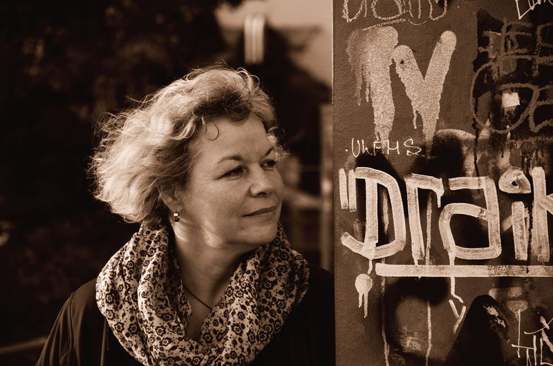 Close-up of thoughtful woman standing by graffiti wall