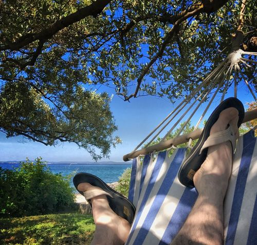 Low Section Human Leg Human Foot Personal Perspective Human Body Part Tree Barefoot One Person Feet Up Relaxation Shoe Vacations Outdoors Day Adult Adults Only Lifestyles Beauty In Nature Sky Water