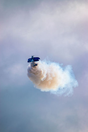 Stunt biplane at airshow pulls up suddenly into the sky leaving a large white vapor trail behind