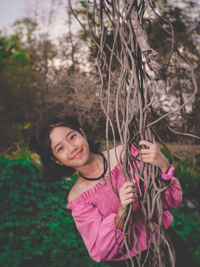 Portrait of smiling girl while holding vines of tree
