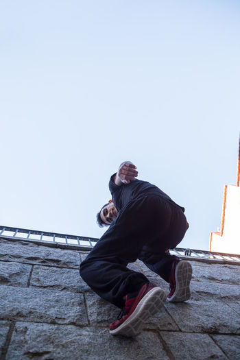 Full Length Portrait Of Man Climbing On Wall Against Clear Sky